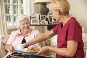 caregiver serving a meal to an elderly woman